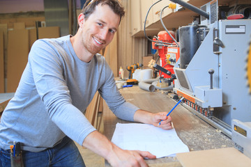 An adult carpenter measuring wood with ruler at table in
