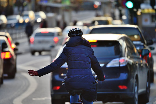 Winter city scene. Woman on bike in traffic