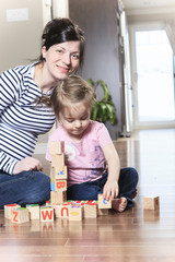 Relaxed mother and daughter playing with building blocks on
