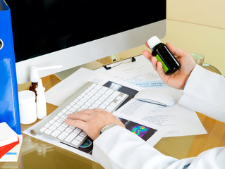 Doctor using a computer to prepare an online prescription or wri