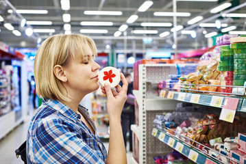 Woman smelling fragrant soaps in department of cosmetics