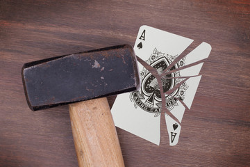 Hammer with a broken card, ace of spades