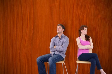Composite image of sitting couple ignoring each other