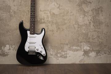 Black guitar near the wall