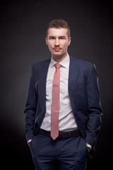 man, suit, hands in pockets, studio