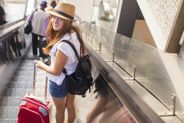 Young girl with the suitcase standing on the escalator. Travel