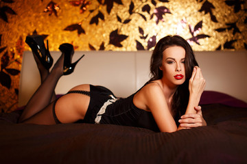 Sexy woman in stockings laying on bed