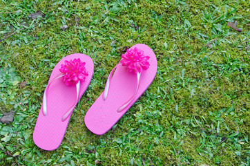 top view of two playful pink flip-flops on green grass