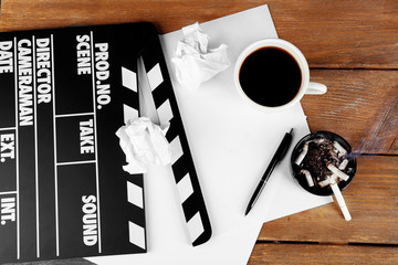 Movie clapper with cup of coffee and ashtray with cigarette