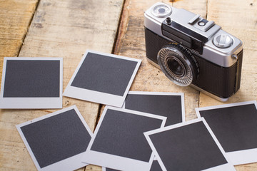Old analog camera with photo frames over wooden table.