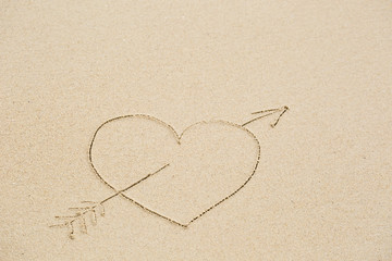 Picture of a heart pierced with an arrow on wet beach sand