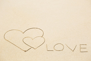 Inscription of Love written on wet yellow beach sand