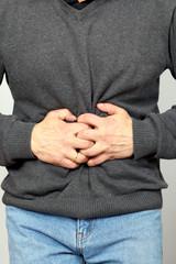Mann mit krampfenden Schmerzen im Bauch