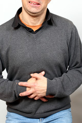 Mann hält sich Bauch, schmerzverzerrter Mund