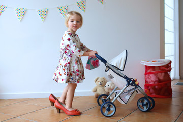 Little girl playing mom's-to-be role walking with pram and doll