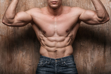 Muscular man showing abs, on wall background