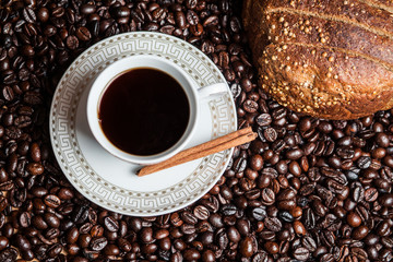 Cup of coffee and black bread on coffee beans
