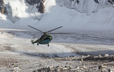 Military helicopter landing on ice of mountain galcier
