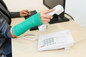Injured businesswoman with green cast on the wrist holding telep