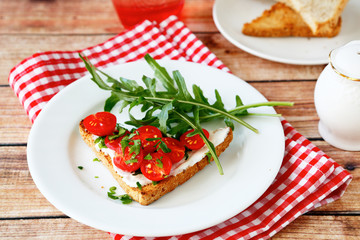 Bruschetta with tomato and arugula on a plate