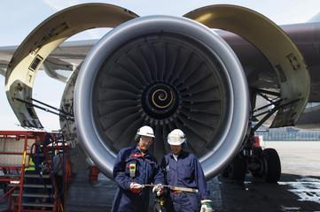 airplane mechanics in front of jumbo jet engine