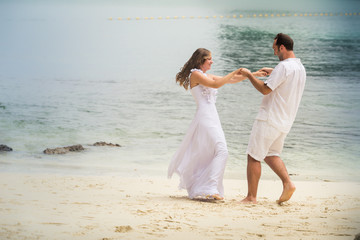 blonde bride and groom dance standing at sand beach