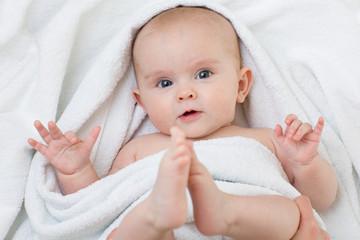 Cute baby lying on white towel