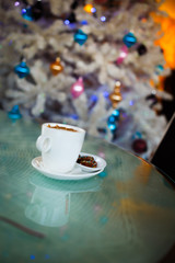 White cup of coffee under the christmas tree
