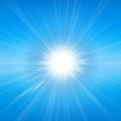 Intense sunlight and sunbeams in a clear blue sky