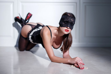 Sexy woman in lace eye cover and underwear kneeling