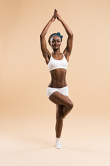 Young African woman in the stretching yoga position