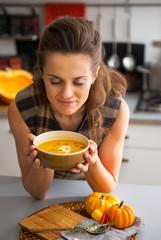 Young woman enjoying pumpkin soup in kitchen