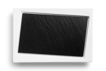Empty white plate with black stone surface isolated on white bac