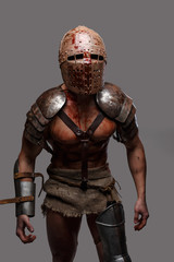 Gladiator with muscular body covered in blood