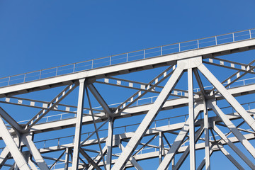 Construction truss bridge on background of blue sky