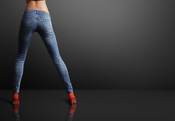 perfect shaped woman wearing skinny jeans in a dark room