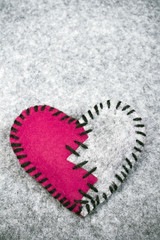 stitched broken felt heart on a on a gray background