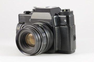 Old black film SLR camera on white background