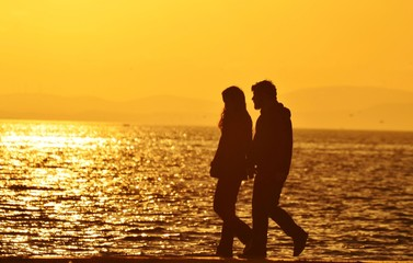 Young couple walking on beach under sunset