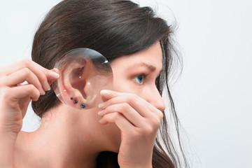 Woman's  ear with three earrings through the magnifying glass