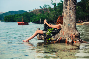 Woman sitting up against tree on tropical beach