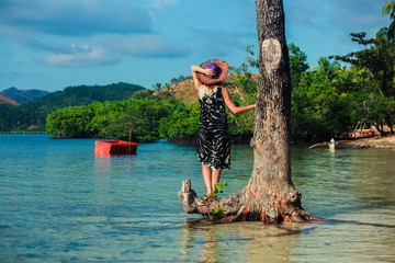 Woman with hat by tree on tropical beach