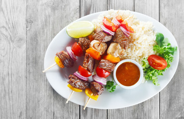 Gourmet Kebabs on Plate with Sauce and Rice