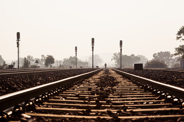 Distant man walking on railway track