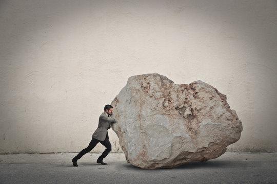 Businessman pushing a boulder