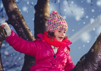 Winterly portrait of a girl climbing on a tree