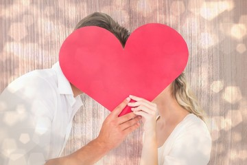 Wall Mural - Attractive young couple kissing behind large heart