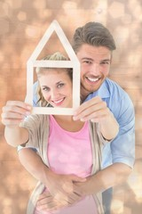 Young couple hugging and holding house outline