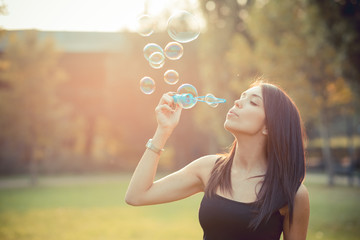 young beautiful brunette straight hair woman blowing soap bubble