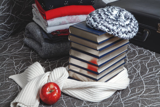 Stack of winter clothes and books with glossy edge